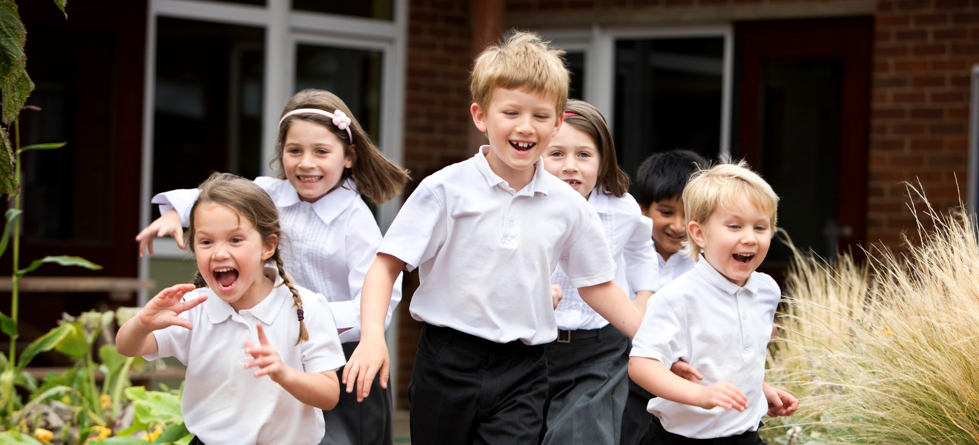 Smiling students running outside.