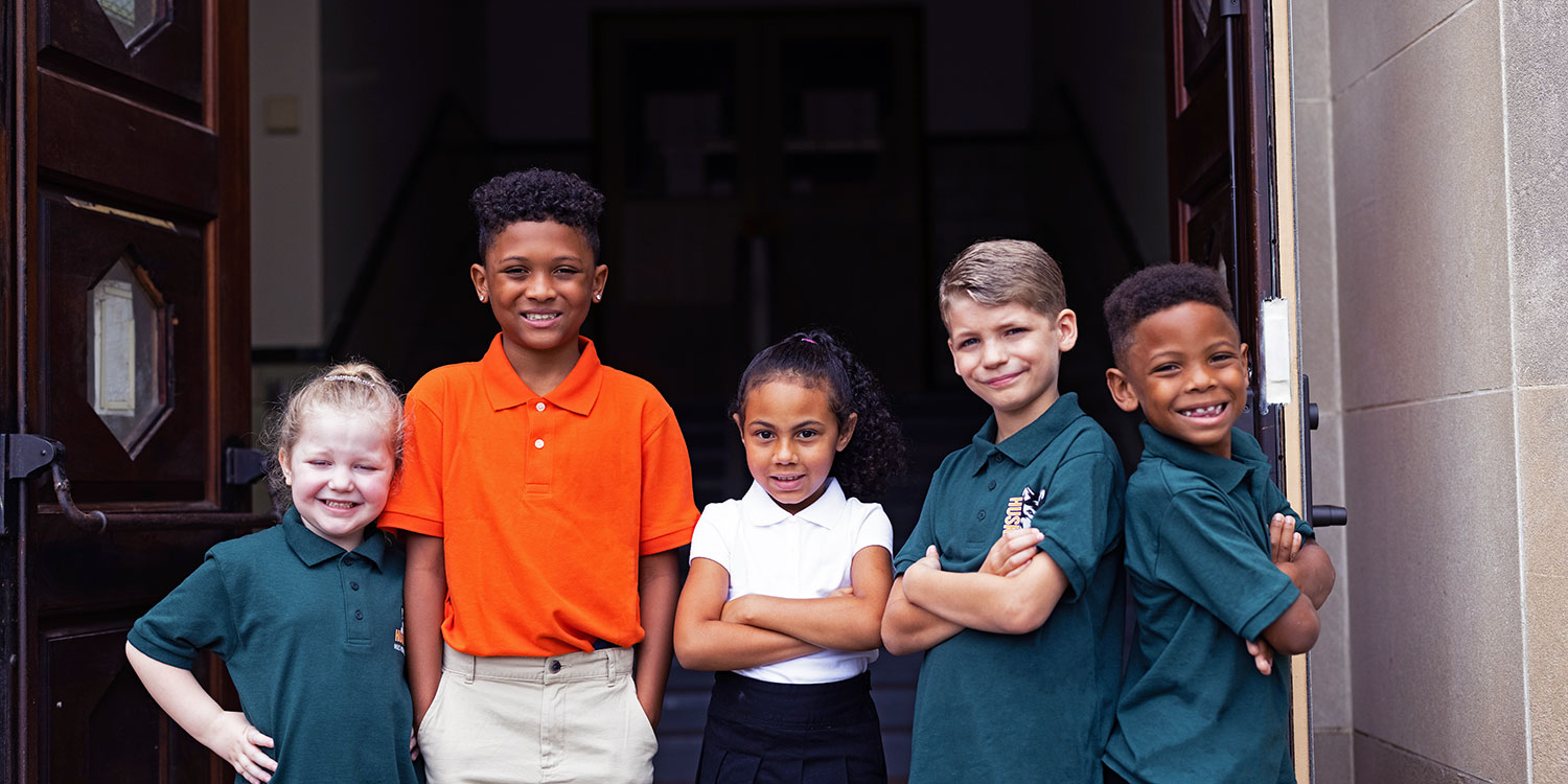 Smiling elementary students standing on Niles Prep front steps.
