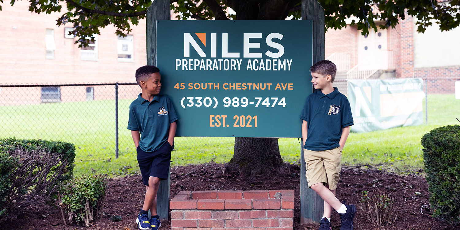 Smiling elementary students standing by Niles Prep sign.