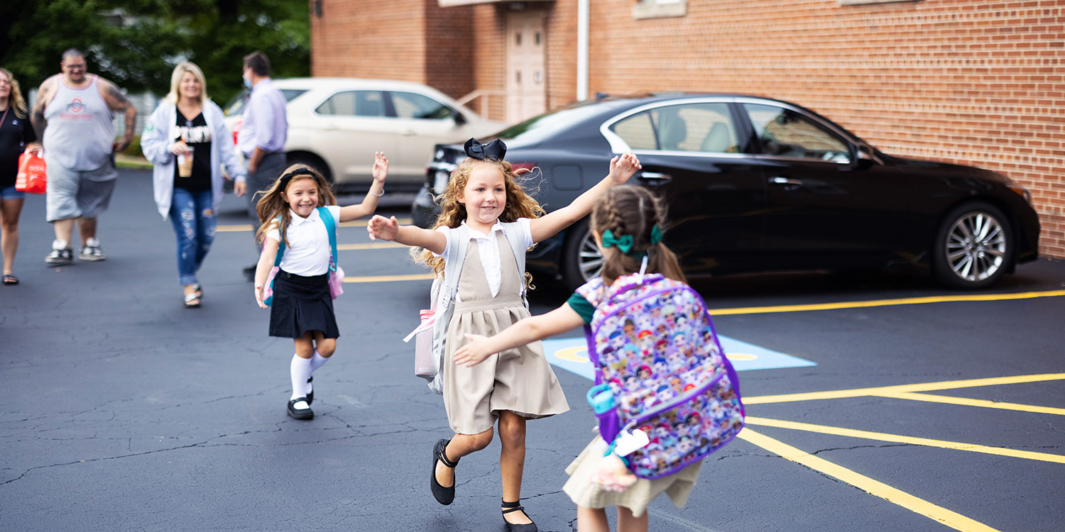 Smiling elementary students running to hug each other.